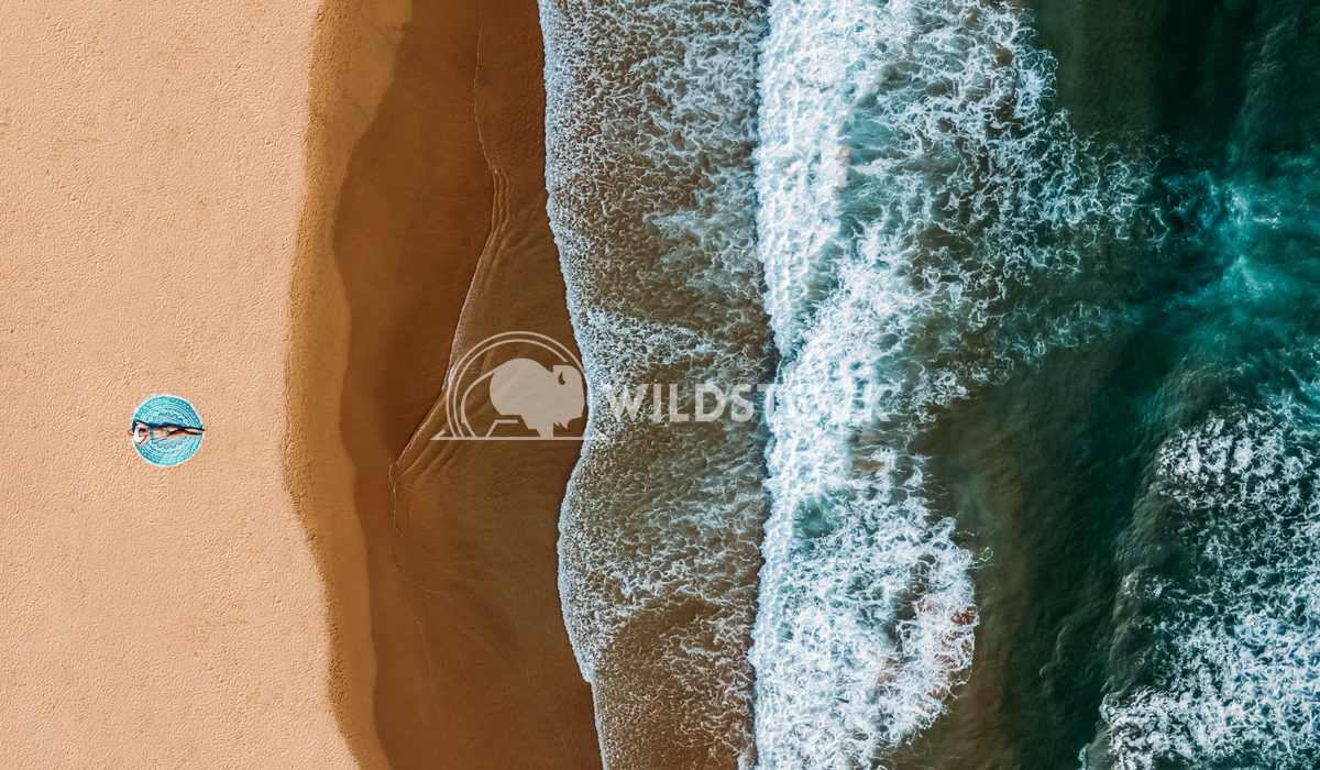 Top Aerial Drone View Of Woman In Swimsuit Bikini Relaxing And Sunbathing On Round Turquoise Beach Towel Near The Ocean