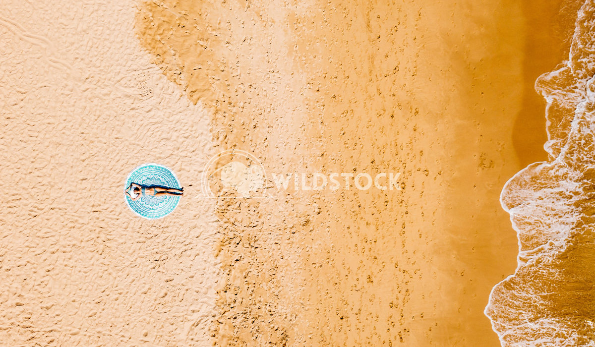 Top Aerial Drone View Of Woman In Bikini Relaxing And Sunbathing On Round Turquoise Beach Towel Near The Ocean Radu Berc