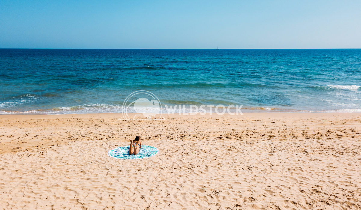Aerial Drone View Of Woman In Swimsuit Bikini Relaxing And Sunbathing On Round Turquoise Beach Towel Near The Ocean Radu